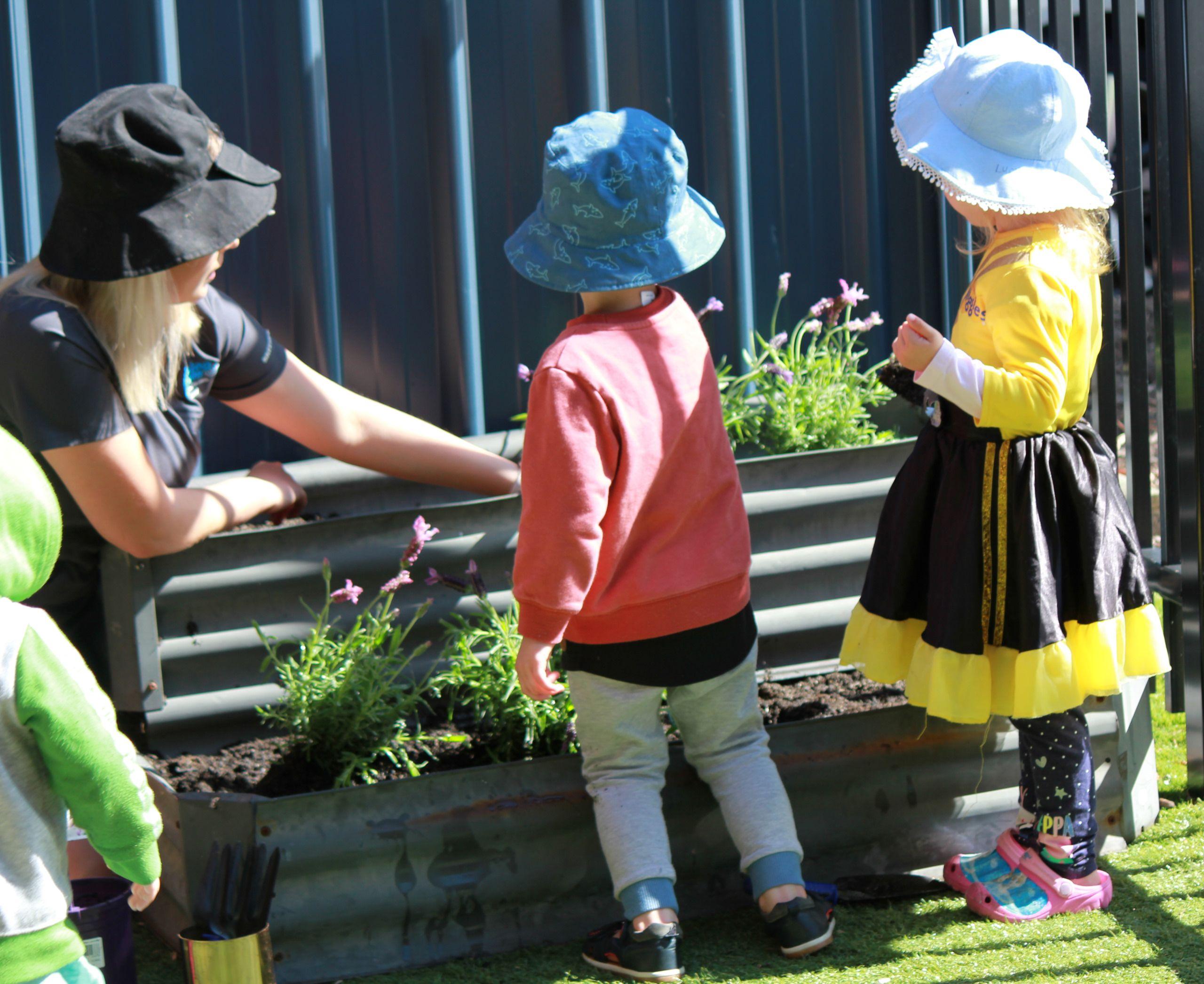 Educator and kids gardening
